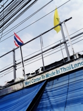 Made in Thailand. Thai and Royal flags with phone and electric wires.