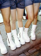 White go-go boots worn by young women trying to attract customers to a beer bar.